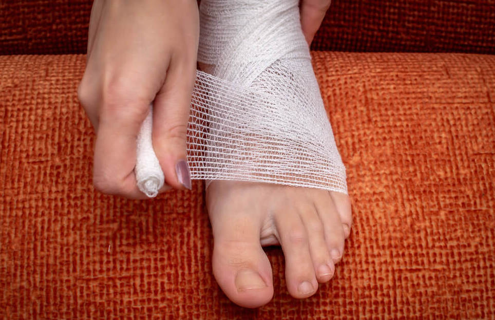 Proper self-help for injuries or bruises in the legs. Wound care bandage, control bleeding.