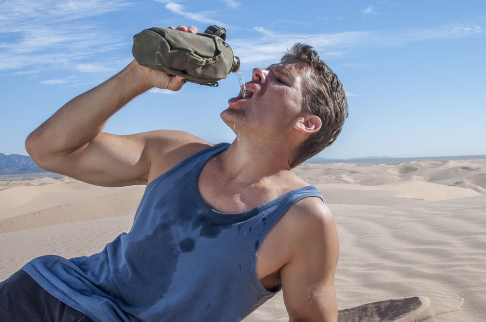 Exhausted dehydrated thirsty hiker in the desert lies down and pours water into mouth